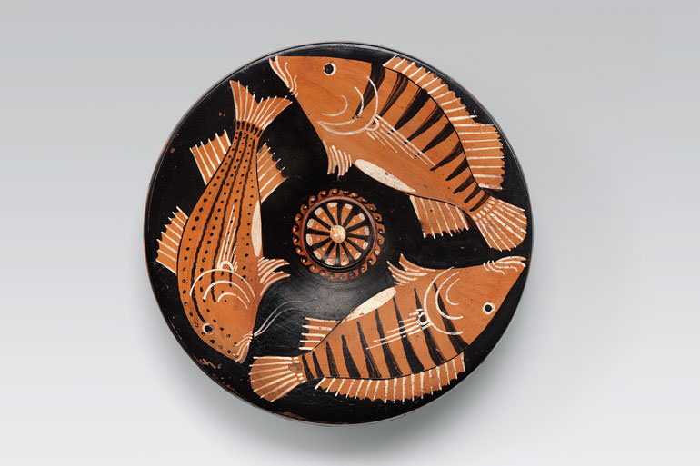 Un piatto di ceramica con raffigurazioni di pesci