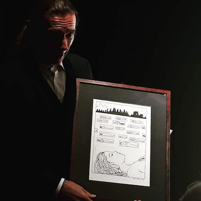 """Paolo Valerio con una tavola di """"Poema a fumetti"""""""