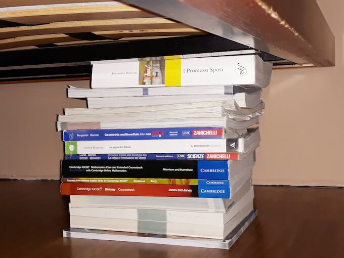 Una pila di libri per sostenere il letto