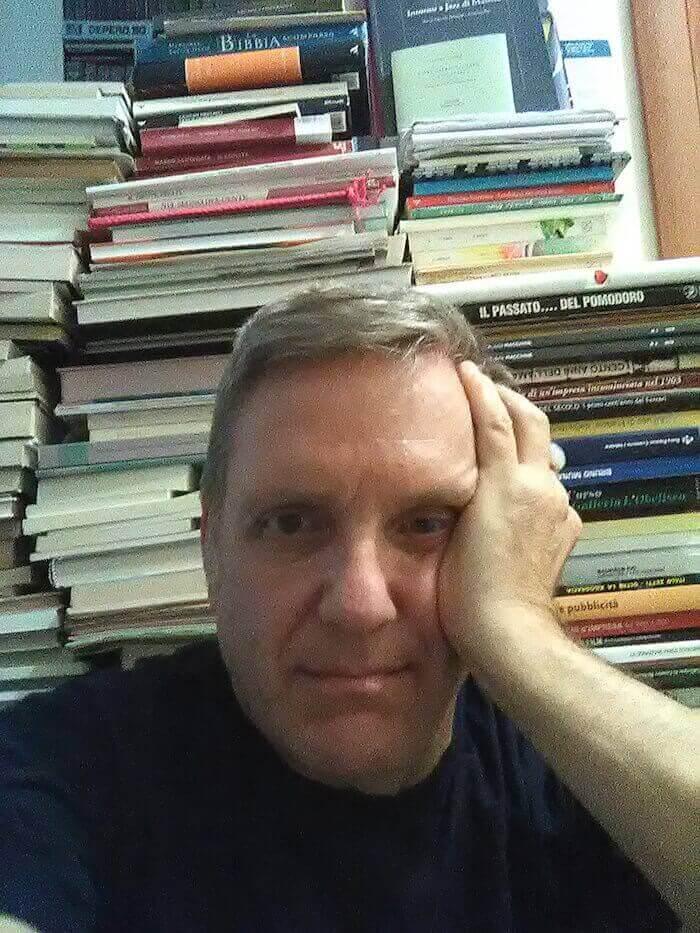 Massimo Gatta davanti a una piccola parte della sua biblioteca